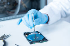Lab engineer working on broken hard disk Stock Photo