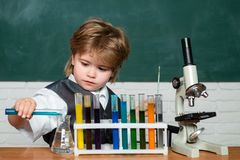 Lab microscope and testing tubes. Little kid scientist earning chemistry in school lab. Child in the class room with royalty free stock images