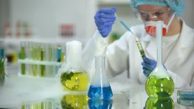 Lab researcher adding blue liquid substance in tube with green plant, test