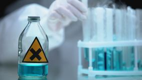 Lab researcher taking from fridge test tube with danger liquid, bottle on table. Stock footage stock video