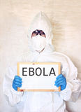 Lab scientist in safety suit holding board with word ebola Royalty Free Stock Image