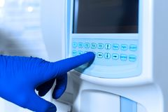 Lab technician adjusts device of very accurate medical blood test.  stock photo