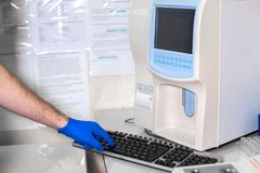 Lab technician adjusts device of very accurate medical blood test.  royalty free stock photos