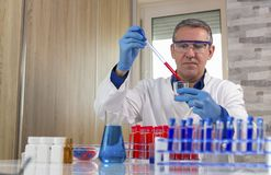 Microbiology Analyst Working with Pipette in Laboratory. Lab technician analyzing blood sample. Researcher wearing blue protective gloves, white uniform and stock photos