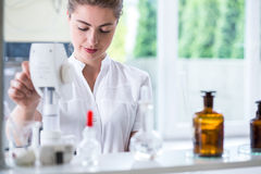Lab technician doing chemistry experiment. Young female lab technician doing chemistry experiment Royalty Free Stock Image
