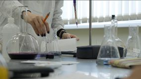 Lab technician doing experiment in lab. Male medical or scientific laboratory researcher performs tests with blue liquid Stock Images