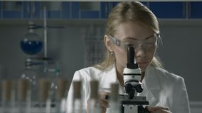 Lab technician doing microscope sample analysis stock video footage