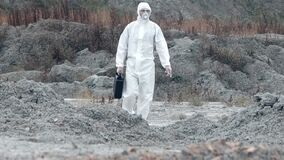 Lab technician in a mask and chemical protective suit, walks on dry ground with a tool box through toxic smoke