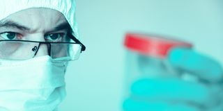 Lab technician, medic. Jar for analysis. On the face of a protective mask. Glasses. Protective suit stock photos