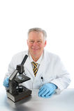 Lab Technician with Microscope. Middle aged lab technician sitting in front of his microscope. Vertical format over white with reflections in table top Royalty Free Stock Images