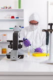 Lab technician using a pipette. A lab technician in sterile clothing using a pipette Royalty Free Stock Image