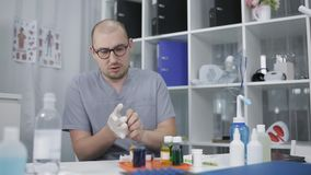 A lab technician wearing glasses at the table puts on rubber gloves. Laboratory studies in the clinic.