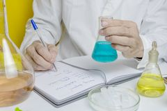 Lab technician writing test note on notebook after doing medical research and development for microbiology in lab. stock photo