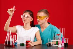 Lab technicians, a girl and a guy, examine the red liquid in a transparent flask that the girl holds in hand. stock photos