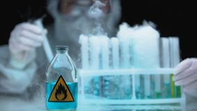 Lab worker analyzing evaporating liquid in tube, bottle with flame sign near