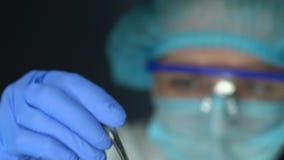 Lab worker in glasses taking pink capsule in forceps, pharmaceutical industry. Stock footage stock video footage