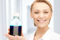 Lab worker holding up bottle with blue liquid Royalty Free Stock Photography