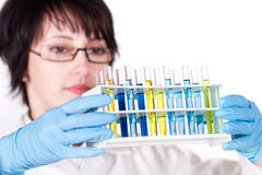 Lab worker holding up test tube. Picture of beautiful lab worker holding up test tube Stock Images