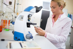 Lab worker look for chemical data at ipod. Female lab worker look for chemical data at ipod in laboratory Stock Photos
