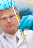 Lab worker testing liquid. Male lab worker inserting a test strip into a test tube of fluid. Focus on the lab worker's hands and test tube with shallow depth of stock photography