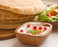 Labane with pita bread and a salad. Greek yogurt in a wooden bowl with pita bread and a salad decorated with min leafs and pomegranate Royalty Free Stock Photos