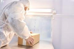 Labbarbetare som packar medicinska produkter arkivbilder