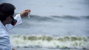 Labbforskare som kontrollerar vattenförorening som orsakas av oljeutsläpp, stads- runoff arkivbild