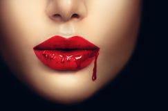 Labbra della donna del vampiro con il sangue della sgocciolatura Immagini Stock