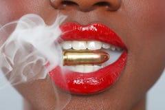 Labbra di una donna con una pallottola e un fumo Fotografia Stock