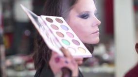 Labbra ed occhi di tiraggio Il truccatore applica il trucco ad un giovane modello attraente per la sessione di foto stock footage