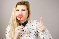Labbra felici di falsificazione della tenuta della donna sul bastone Fotografie Stock