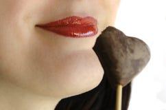 Labbra rosse che sorridono con il biscotto di cuore-forma del cioccolato Immagini Stock