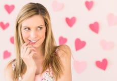 Labbro mordace della donna con le carte a forma di del cuore contro Backgr colorato Immagine Stock