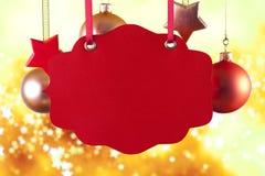 Label, babioles de Noël et étoiles rouges Photos stock