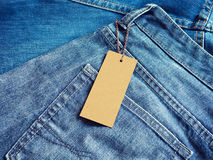 Label blank price tag mockup on blue jeans. Royalty Free Stock Images