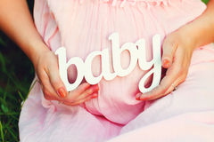 Label the child in the hands of a pregnant woman Royalty Free Stock Photography