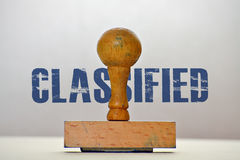 Label Classified. Rubber stamp and word Classified on bright background Royalty Free Stock Images