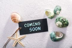 Label with coming soon. A natural looking label with coming soon written on it with sand and seashell and star stock images