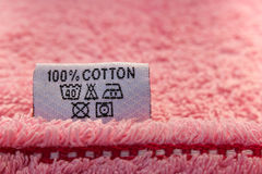 Label 100% cotton on pink towel. The inscription on English languages Stock Photo