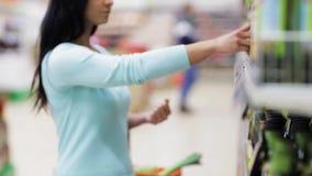Label de lecture de femme sur la bouteille d'huile d'olive à la boutique clips vidéos