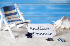 Label With Deck Chair, Endlich Sommer Means Happy Summer. Summer Label With German Text Endlich Sommer Means Happy Summer. Blue Wooden Background. Card With stock images