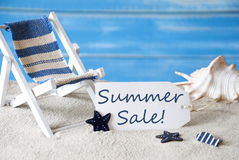 Label With Deck Chair And Text Summer Sale. Summer Label With English Text Summer SaleBlue Wooden Background. Card With Holiday Greetings. Beach Vacation Stock Photography