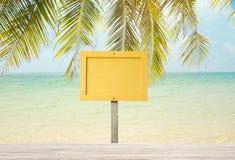 Label en bois jaune vide de signe sur la plage de mer Image stock