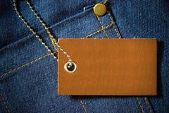 Label en cuir de prix de produit et de chaîne inoxydable de bille d'acier sur l'habillement de denim photographie stock libre de droits