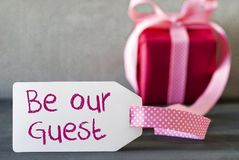 Pink Gift, Label, Text Be Our Guest. Label With English Text Be Our Guest. Pink Gift Or Present With Gray Cement Background Royalty Free Stock Image