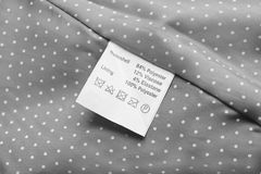 Label. Fabric composition label on gray cloth as a background Stock Photography