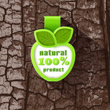 Label in the form of an Apple. On a background of tree bark. 100% natural product Stock Images