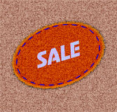 Label in the form of a patch on a fabric background with the text of sale Royalty Free Stock Images