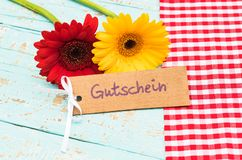 Label with german word, Gutschein, means voucher or coupon with beautiful flowers. Gerbera daisy flowers with label with german word, Gutschein, means voucher or Royalty Free Stock Images