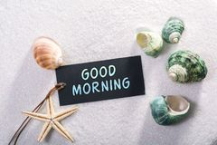 Label with good morning. A natural looking label with good morning written on it with sand and seashell and star royalty free stock images